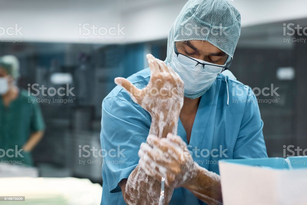 Male veterinarian washing hands with soap stock photo
