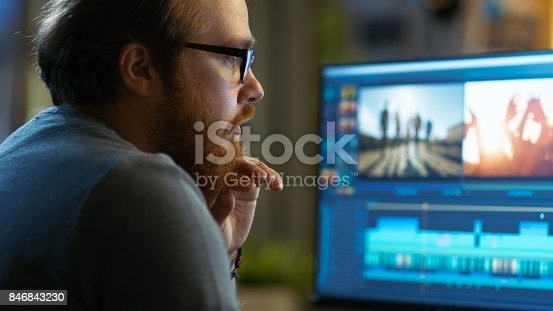 istock Male Video Editor Works with Footage and Sound on His Personal Computer. He Works in a Cool Office Loft. 846843230