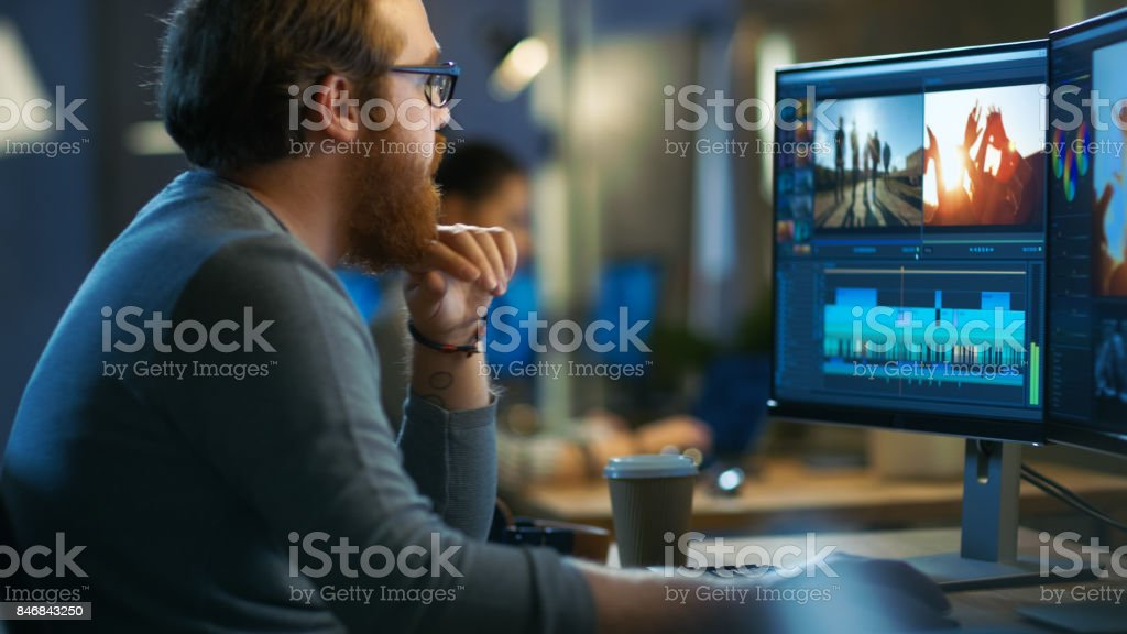 Male Video Editor Works with Footage and Sound on His Personal Computer with Two Displays. He Works in a Cool Office Loft with Other Creative People. stock photo