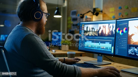 istock Male Videographer Edits and Cuts Footage and Sound on His Personal Computer, Puts on His Monitors/ Headphones. His Office is Modern and Creative Loft Studio. 846843212
