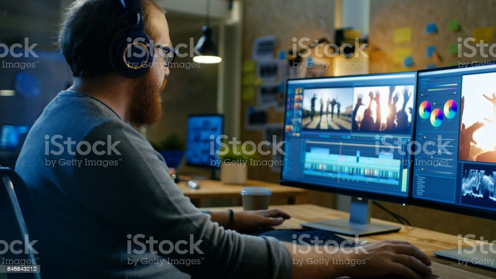 Male Videographer Edits and Cuts Footage and Sound on His Personal Computer, Puts on His Monitors/ Headphones. His Office is Modern and Creative Loft Studio. stock photo