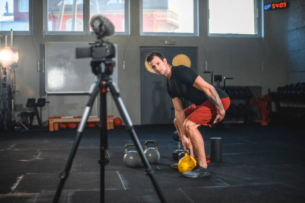 Male Vlogger Filming Tutorial About Kettlebell Deadlifting stock photo