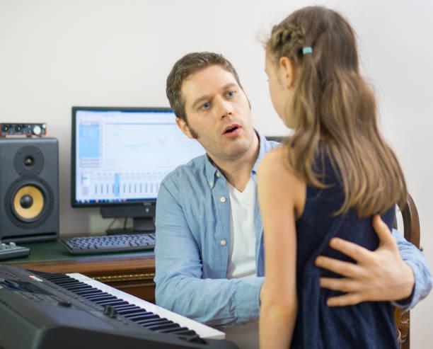 männlicher vocal coach kleines mädchen das singen beizubringen. konzentrierte sich auf lehrer. - one song training stock-fotos und bilder