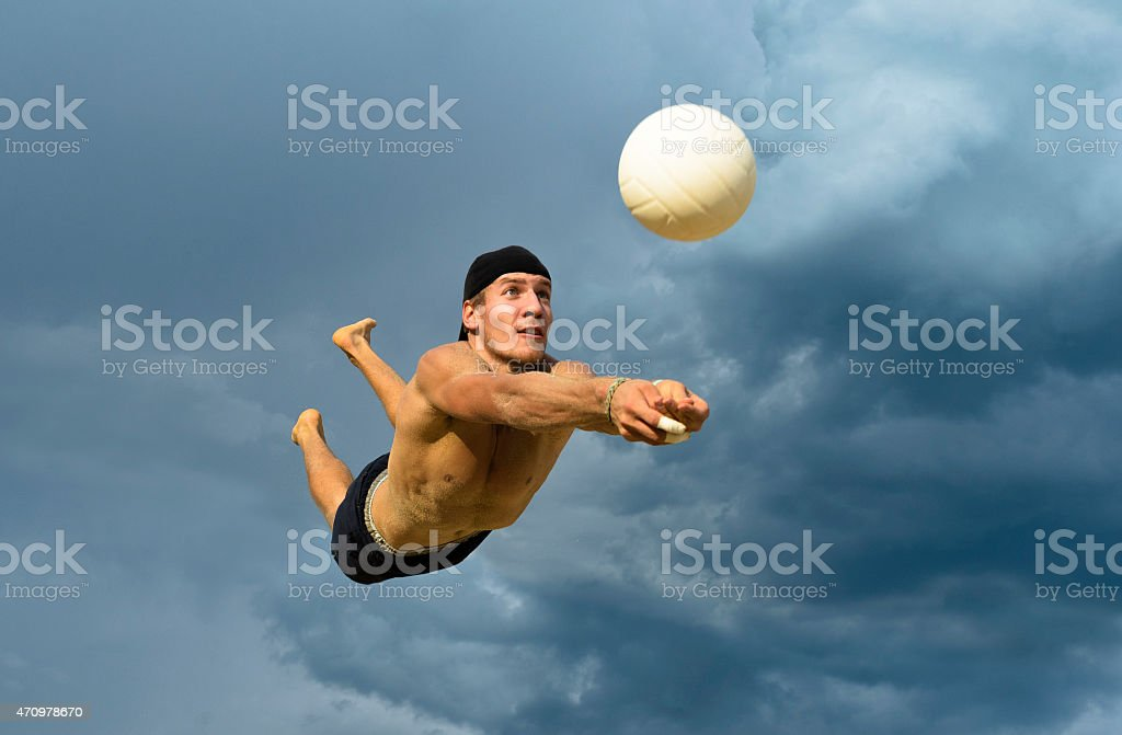Male volleyball player in attractive action against the cloudy sky stock photo