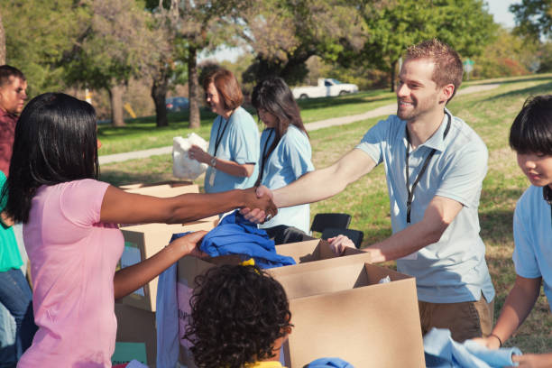 male volunteer greets woman during clothing drive - community project stock photos and pictures