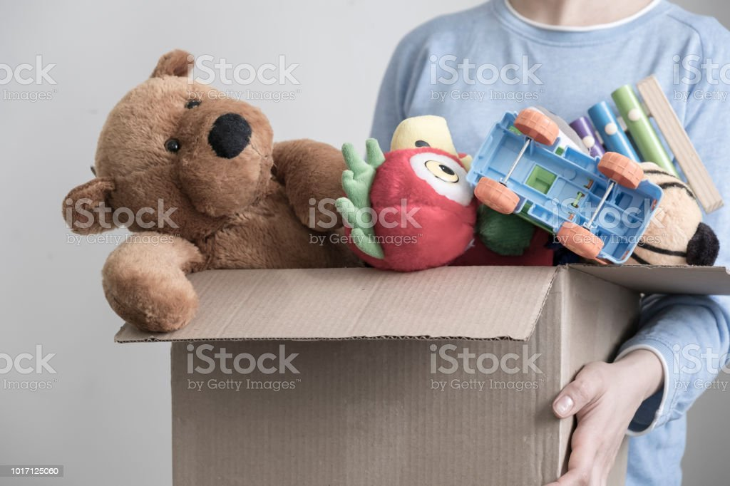 Male volunteer holding donation box with old toys stock photo