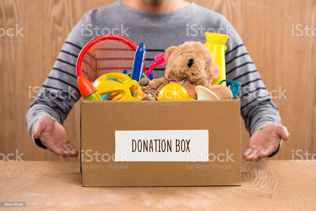 Male volunteer holding donation box with old toys. stock photo
