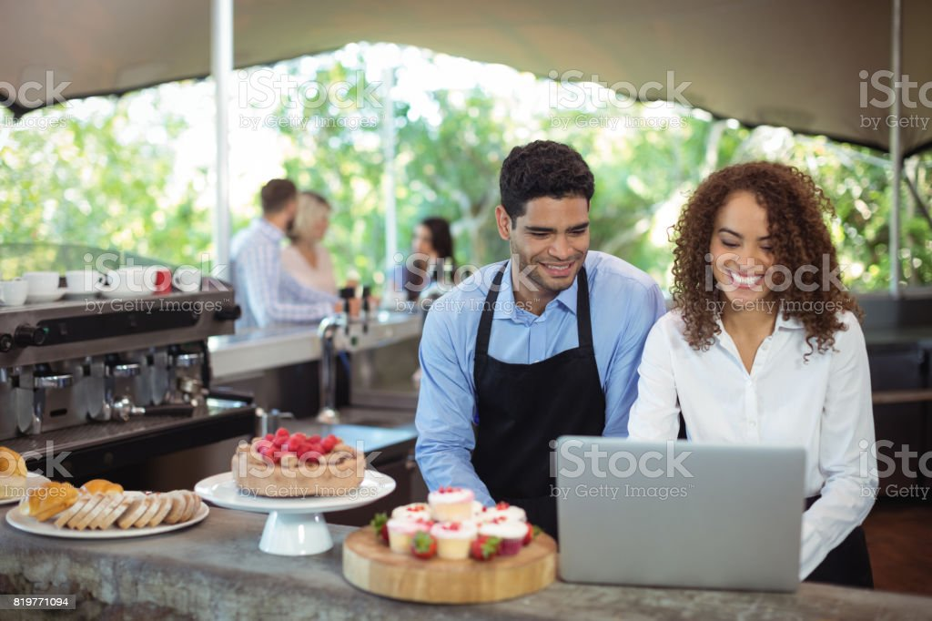 Male waiter and female waitress with laptop stock photo