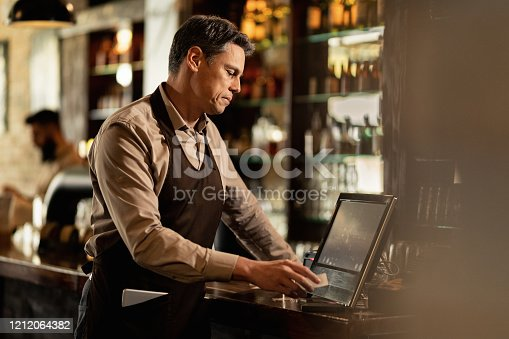 Mid adult barista checking orders at cash register while working in a pub.