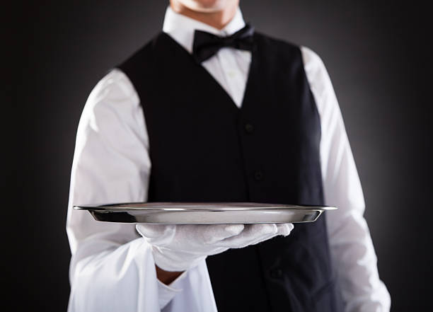 Male Waiter Holding Tray Portrait Of A Male Waiter Holding Tray Over Black Background waiter stock pictures, royalty-free photos & images