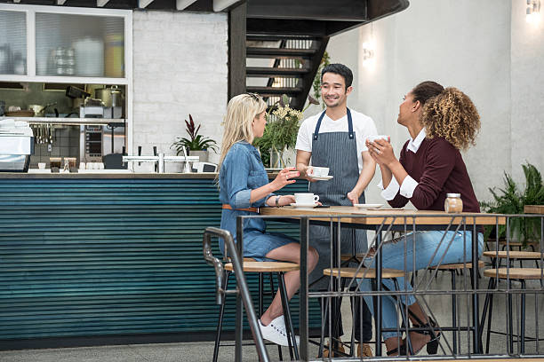 Male waiter serving two young women in cafe stock photo