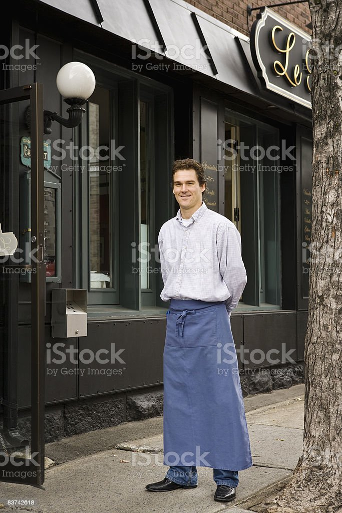 Male waiter standing outside restaurant royalty-free stock photo