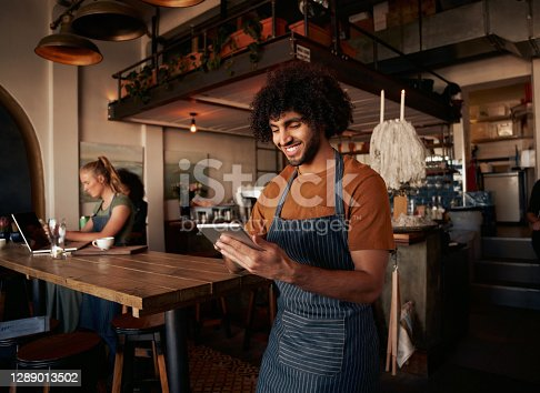 Male waiter working in cafe using digital tablet with female working in background on laptop