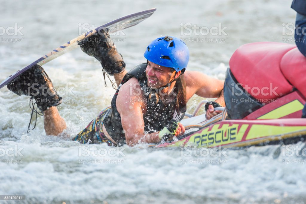 Male wakeboarder fallen into the water holding on jet ski stock photo