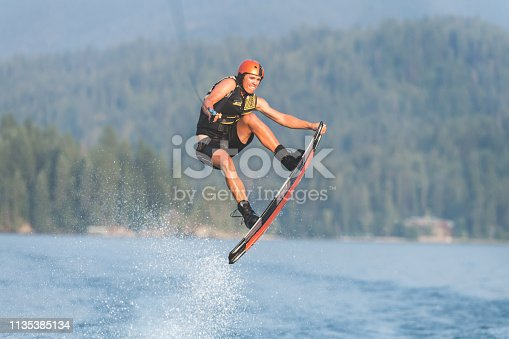 A teenage male wakeboarder launches into the air and grabs his board with one hand while he's upside down.  There are mountains and trees in the distant background.