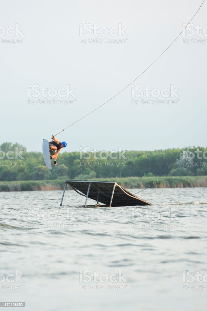 Male wakeboarder performing midair stunts jumping off ramp stock photo