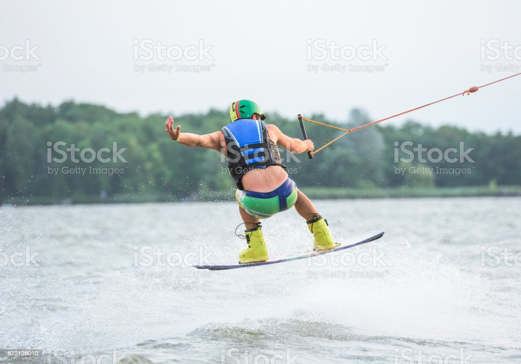 Male wakeboarder riding on lake stock photo