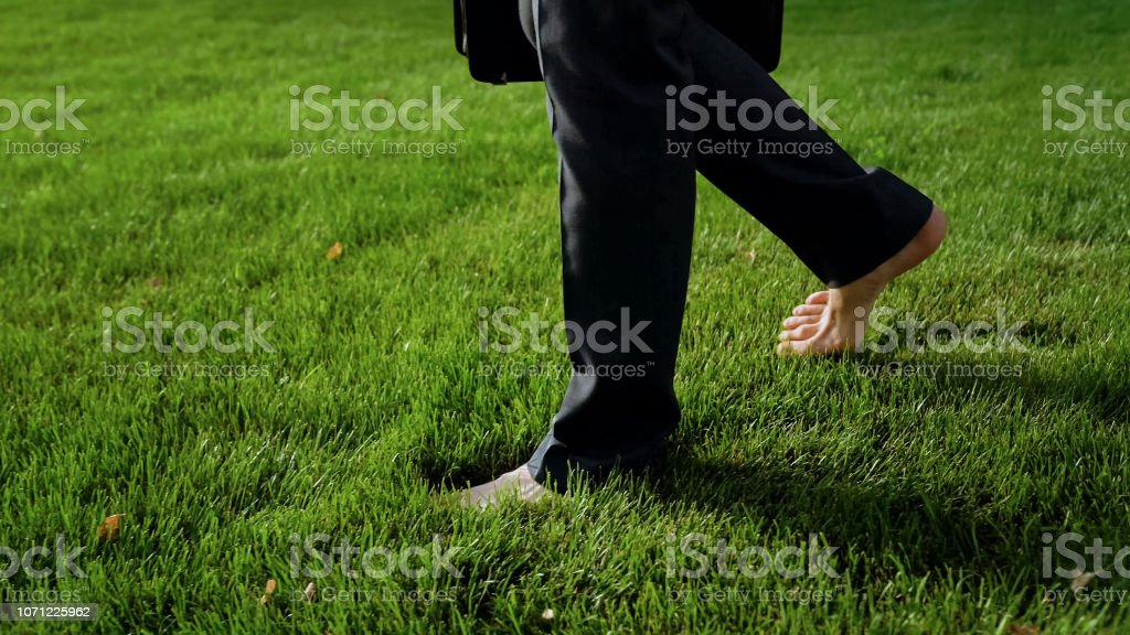 Male walking barefoot on green grass, relaxing after work, dreams...