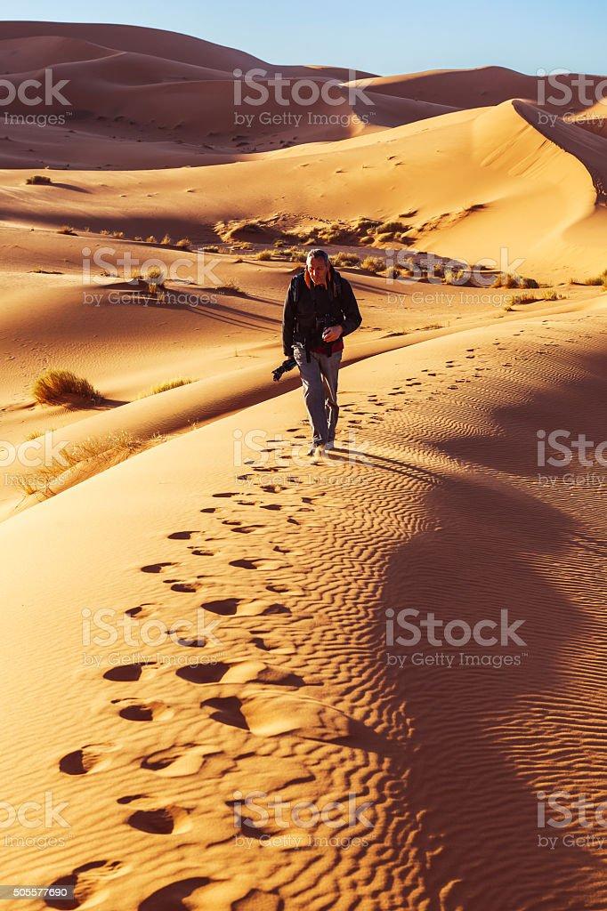 Male walking on the sand dunes, morning, Erg Chebbi, Morocco stock photo