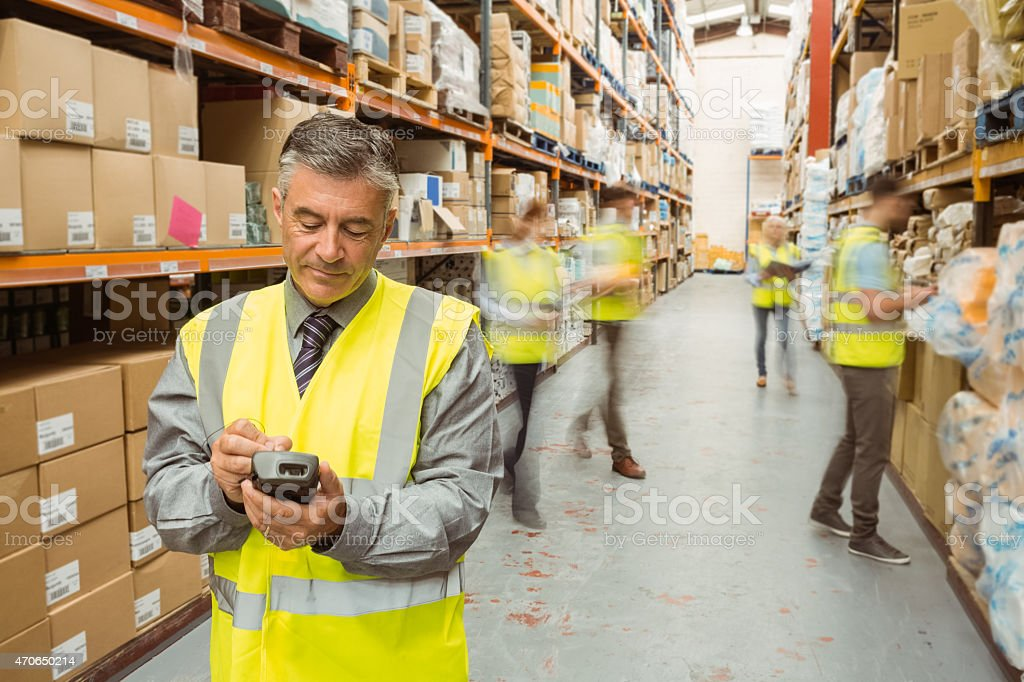 Male warehouse manager checking stock on a handheld device stock photo
