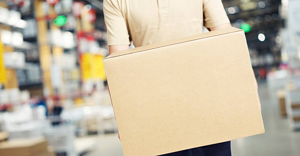 male warehouse worker carrying a carton box male warehouse worker carrying a carton box of goods in a cash & carry wholesale store. food warehouse stock pictures, royalty-free photos & images