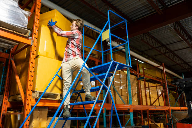 A male warehouse worker climbs a rolling ladder incorrectly. stock photo