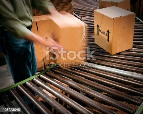 istock Male Warehouse Worker handing Cardboard Boxes and Conveyor Belt. 108223046
