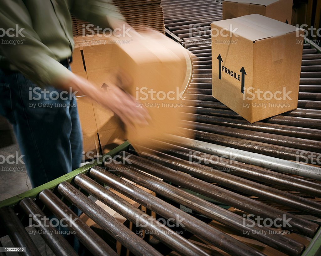 Male Warehouse Worker handing Cardboard Boxes and Conveyor Belt. stock photo