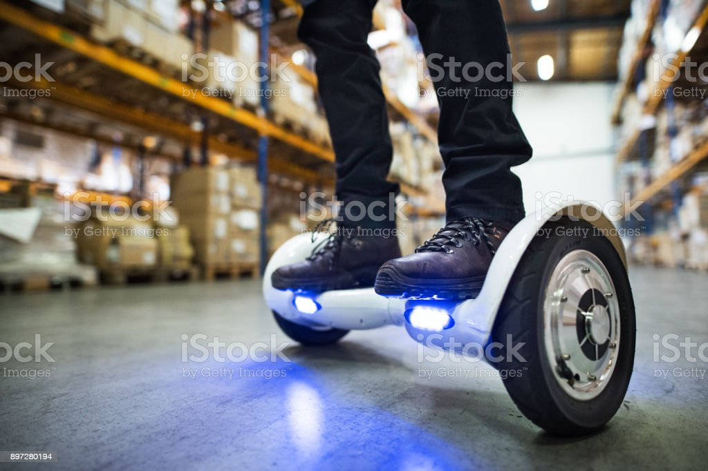 Male warehouse worker on hoverboard. stock photo