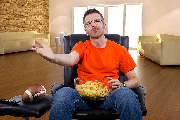 Male Watching Football with Snacks stock photo