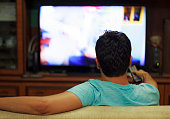 istock Male watching television in home living room / channel hopping 1032604300