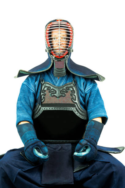 Male wearing a kendo armor with helmet and gloves, sitting position. stock photo