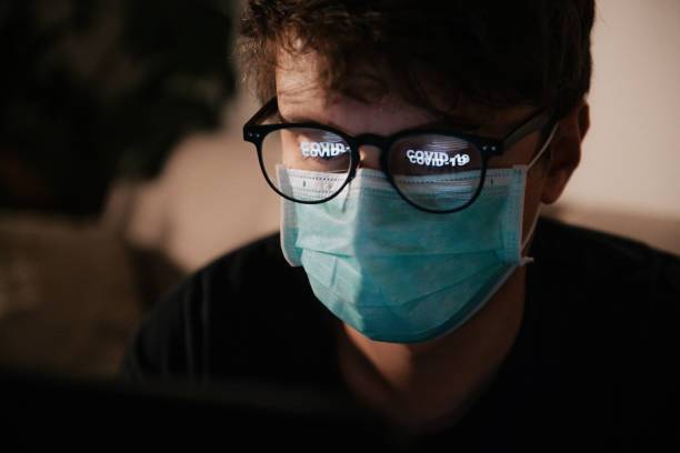 Male wearing protective face mask with reflection COVID-19 in his glasses stock photo
