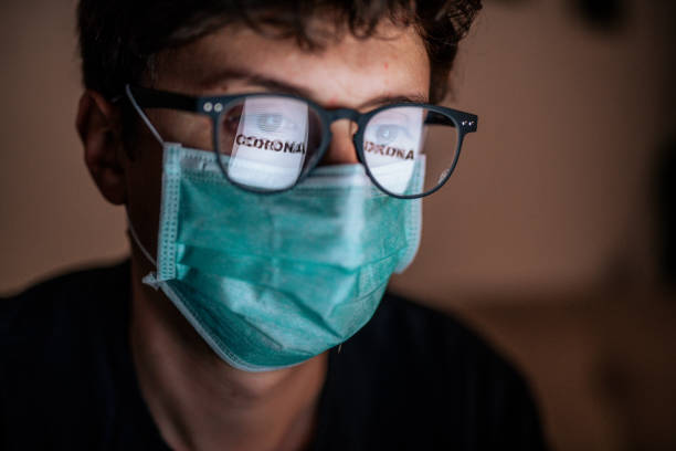 Male wearing sterile face mask with reflection Coronavirus in his glasses stock photo