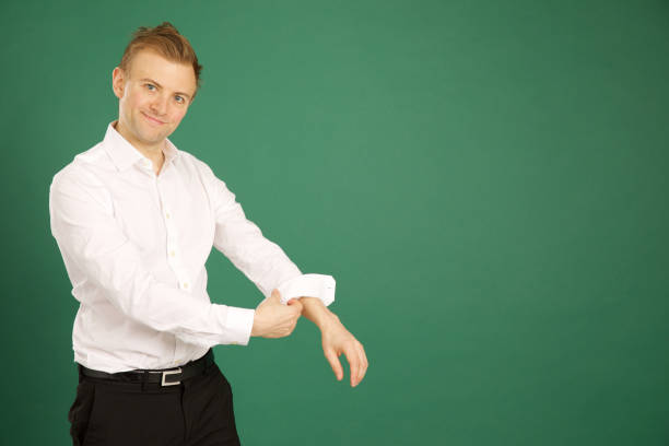 Male wearing white suit and rolling up sleeves stock photo