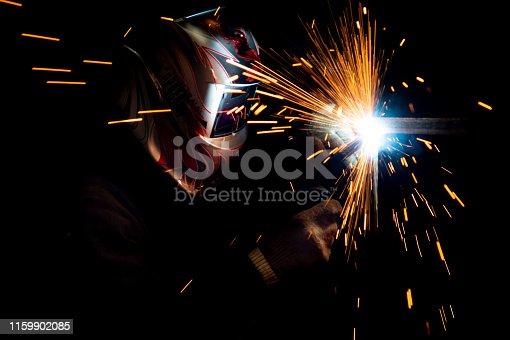 male welder in a mask performing metal welding. photo in dark colors. sparks flying.