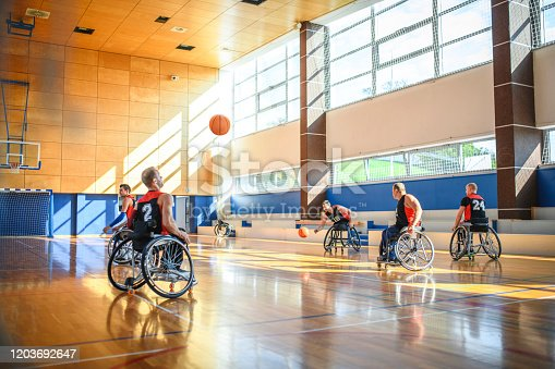 Wheelchair basketball players in 20s and 30s doing shooting drill on court.