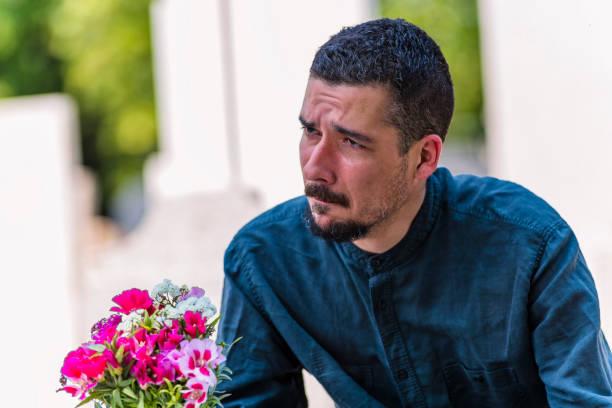 mannelijke weduwnaar in verdriet met rose bloemen boeket op het kerkhof - funeral crying stockfoto's en -beelden