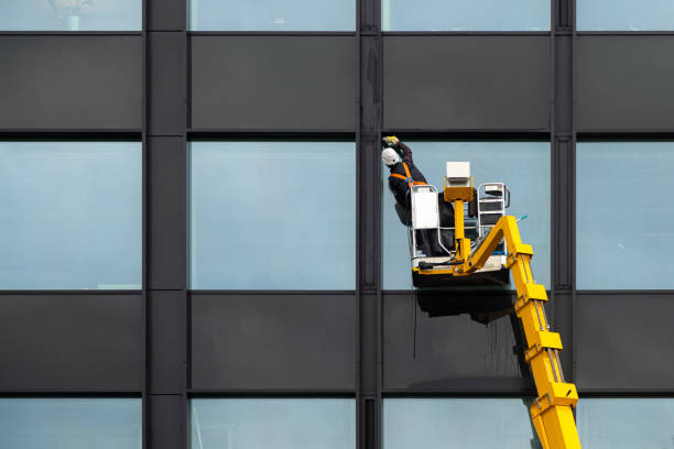 Männliche Fensterputzer putzen Glasfenster auf dem modernen Gebäude hoch in der Luft auf einer Aufzugsplattform. Arbeiter polieren Glas hoch in der Luft – Foto