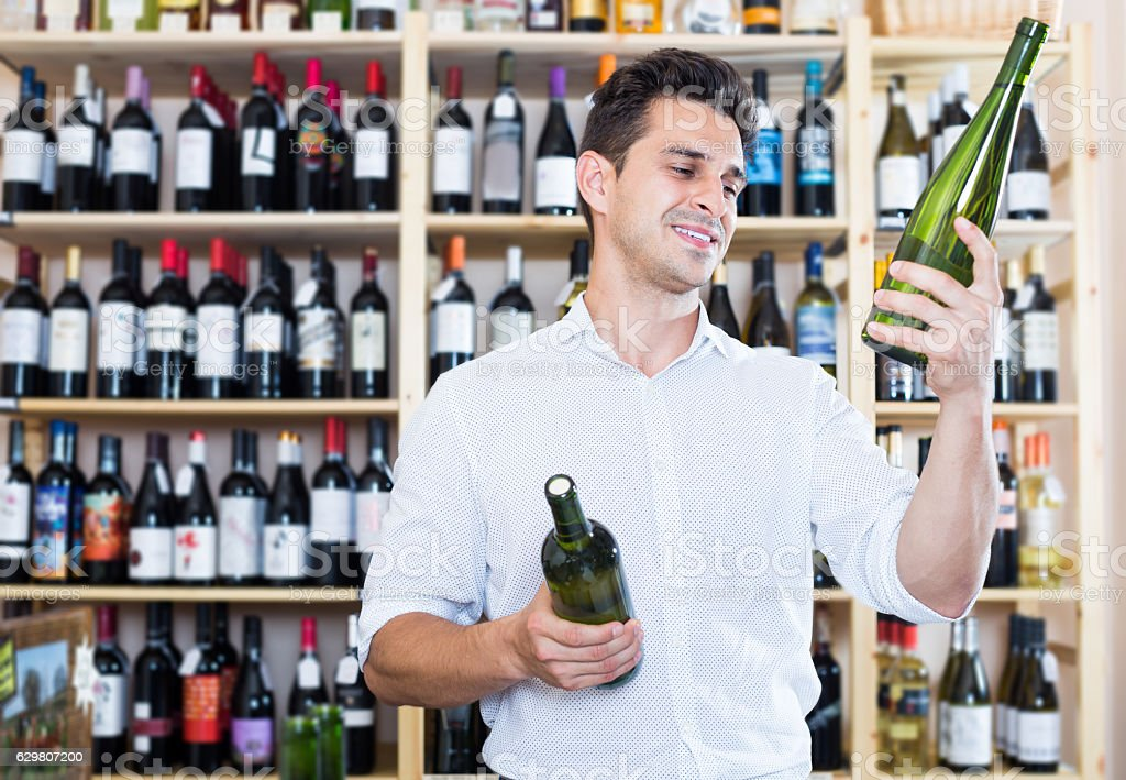Male wine expert holding wine bottles in winery section stock photo