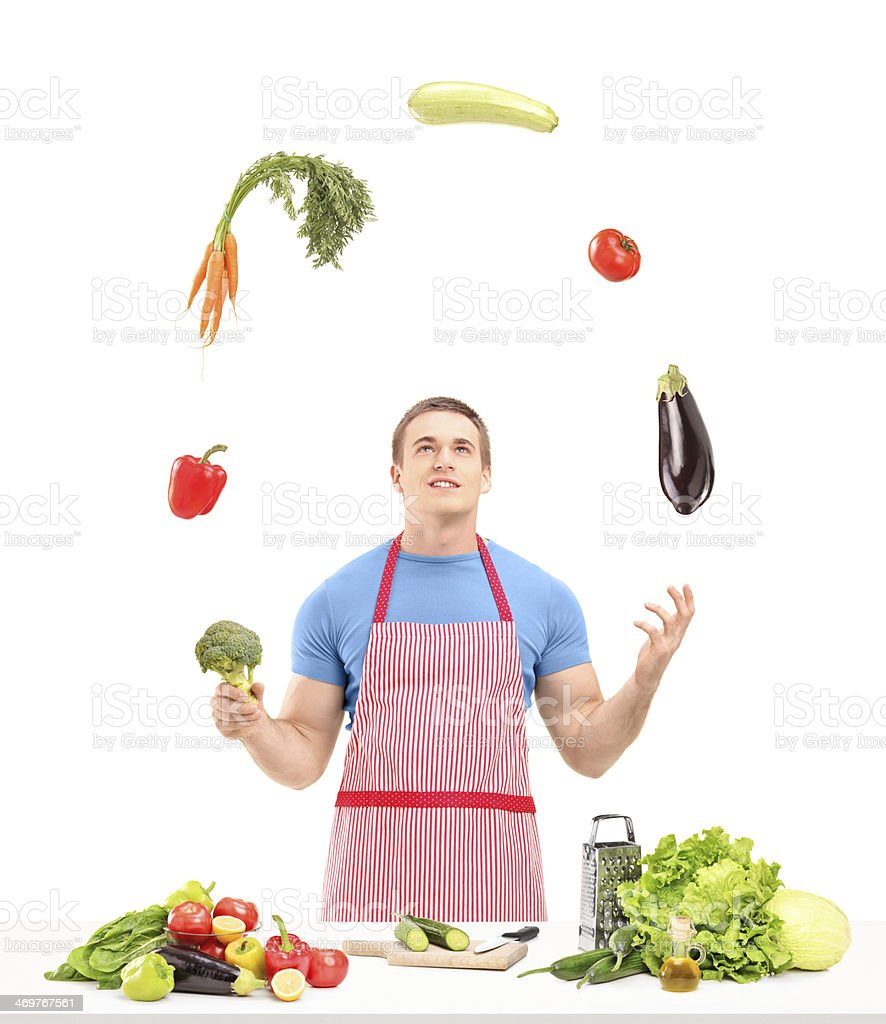 Male with apron juggling vegetables while preparing food stock photo