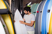 portrait of professional male with board for surfing in the shop
