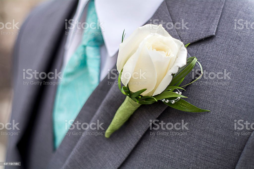 male with grey suit and rose boutonniere stock photo