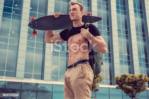 istock Male with longboard showing his muscular stomach. 983234594