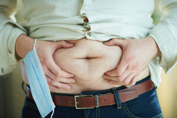 male with medical mask checking body fat by grabbing stomach stock photo