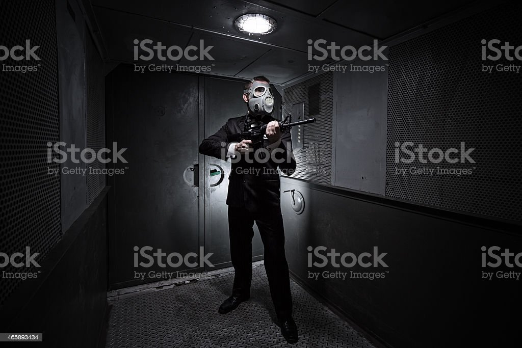 Male with the rifle and gas mask stock photo
