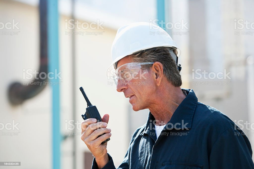 Male worker at industrial plant on walkie-talkie stock photo