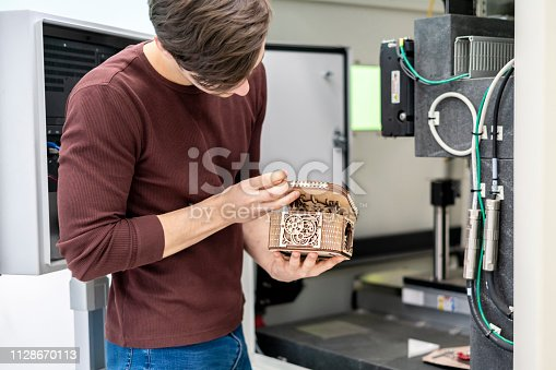 istock male worker carve wood with laser system b 1128670113