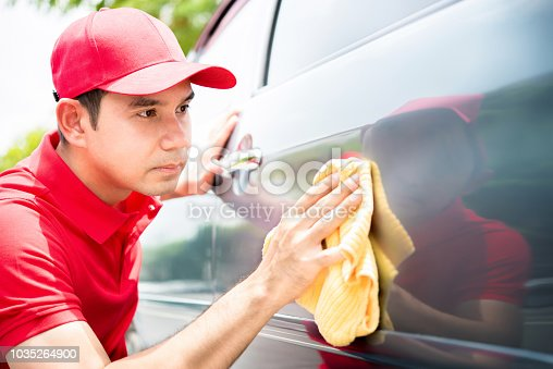 istock Male worker cleaning and looking at car door seriously 1035264900