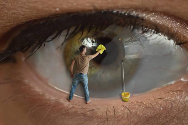 male worker cleaning the surface of the pupil of the eye with a rag. concept of healthy eyesight, conjunctivitis and window cleaning. - soczewka gałka oczna zdjęcia i obrazy z banku zdjęć